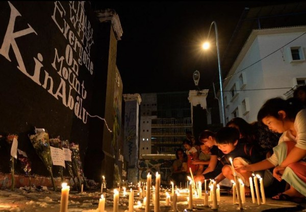 People light candles in memory of the earthquake victims in Kota Kinabalu, on June 7, 2015.